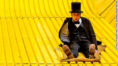 Abraham Lincoln, portrayed by George Buss through the Looking for Lincoln program and the Abraham Lincoln National Heritage Area, speeds past Illinois State Troopers Joe Dattoli, left, Joseph Rush, Trevor Schlindwein, Jeremy Nairn and Jason Wilson as they take a trip down the Giant Slide during the 2019 Illinois State Fair, Sunday, Aug. 18, 2019, in Springfield, Ill. [Justin L. Fowler/The State Journal-Register via AP)