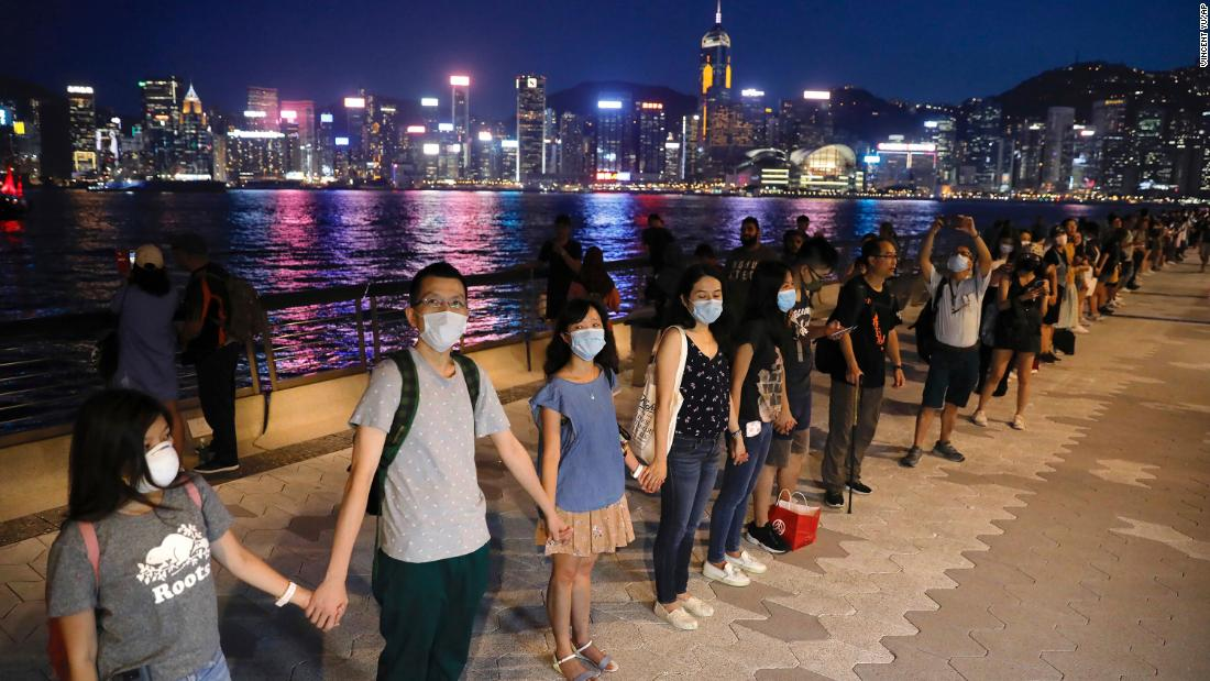 People link hands as they gather at the Tsim Sha Tsui waterfront on Friday, August 23. Protesters formed a human chain across Hong Kong in a show of solidarity.