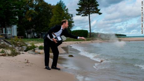 Kyle Haines tosses his husband's ashes into the water at a location they frequently visited together in Mackinaw City, Michigan.