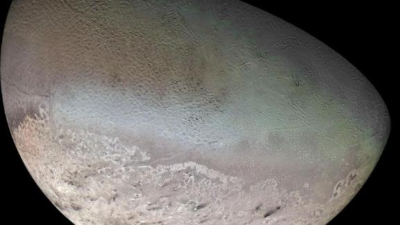 Neptune's largest moon, Triton, surprised scientists with its active surface. Methane ice, shown with a pink tone, may comprise a massive polar cap on the moon's surface. The dark swaths over the ice are likely dust that land from plumes erupting on the surface.