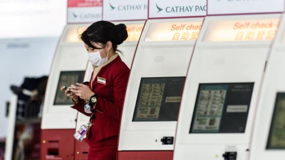 A Cathay Pacific employee walks past a row of self check-in counters at the international airport in Hong Kong on March 15, 2017.  Hong Kong