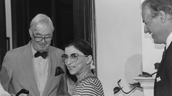 Ginsburg talks with a reporter after being nominated for the Supreme Court in 1993. On the far right is US Sen. Joe Biden. US Sen. Daniel Patrick Moynihan is wearing the bowtie.