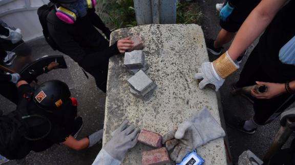 Protesters pick up bricks to be used as projectiles on August 24.