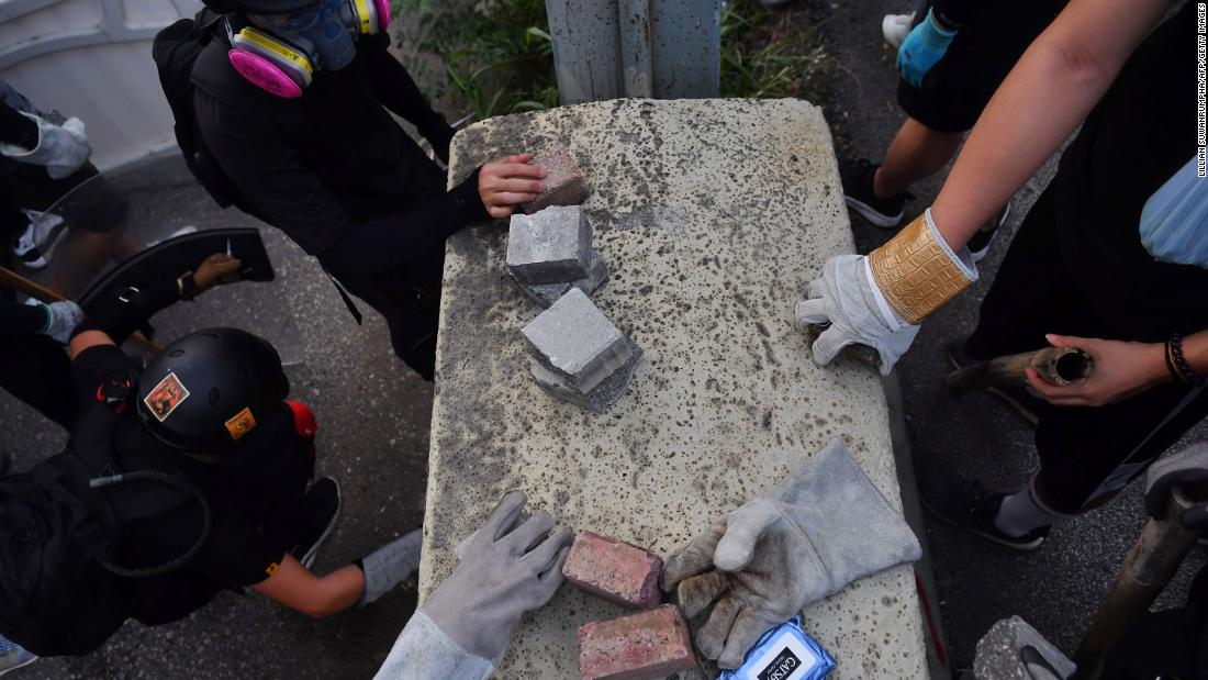 Protesters pick up bricks to be used as projectiles on August 24.<br />