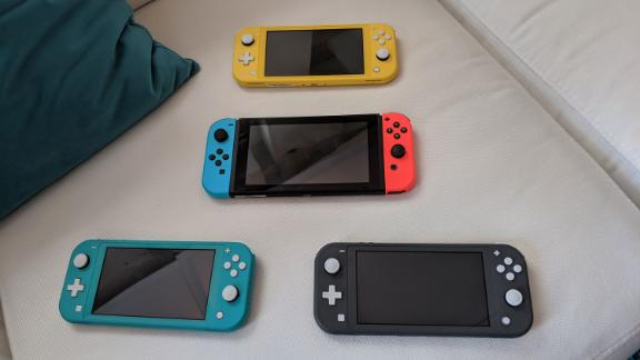 The original Nintendo Switch with blue and red Joy-Cons is accompanied by the Switch Lite in yellow, turquoise and gray.