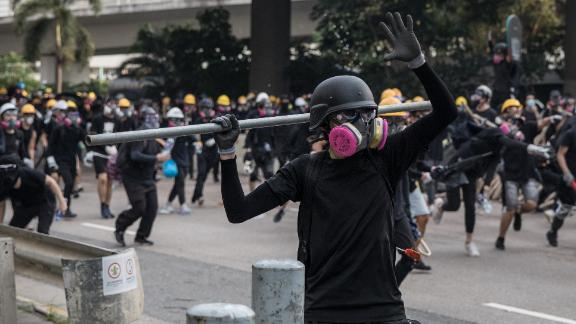 A protester prepares to throw a metal pole during clashes after a rally in Kwun Tong on Saturday.
