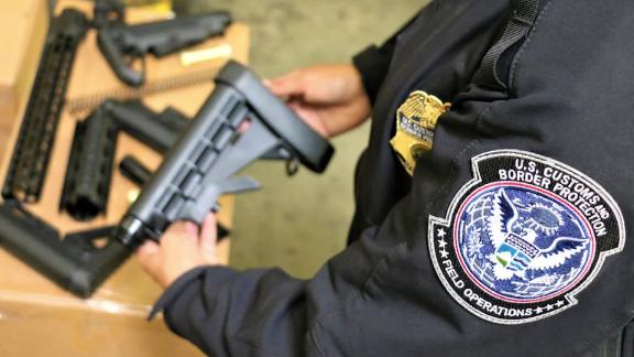 A CBP officer holds one of the seized firearms parts.