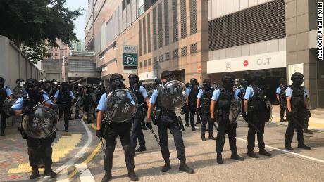 Police holding shields assemble near protest in Kun Tong, Hong Kong on August 24, 2019.