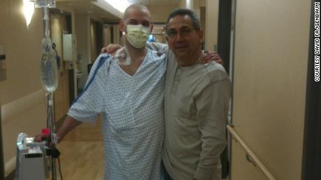 David Fajgenbaum poses with his father during one of his hospitalizations.