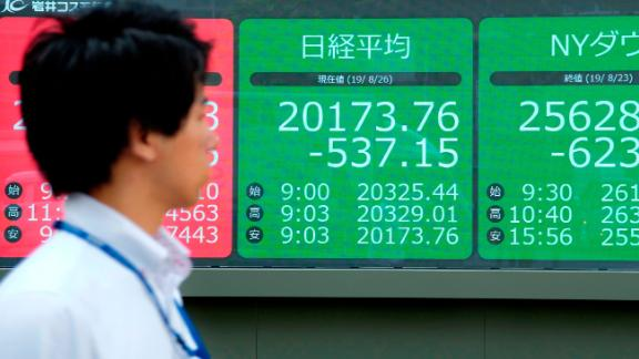 A pedestrian looks at an electric quotation board displaying the numbers on the Nikkei 225 index at the Tokyo Stock Exchange (L) and the the New York Dow (R) in Tokyo on August 26, 2019. - Tokyo's key Nikkei index plunged as much as 2.6 percent at the open on August 26 as the yen surged against the dollar on escalating US-China trade tensions.