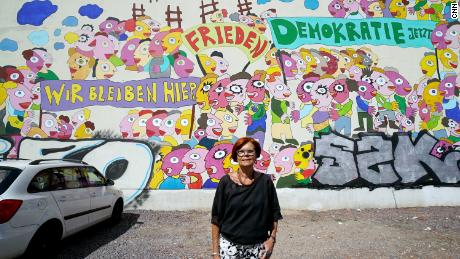 Retired Greens MEP Gisela Kallenbach poses in front of a mural depicting the 1989 protests.