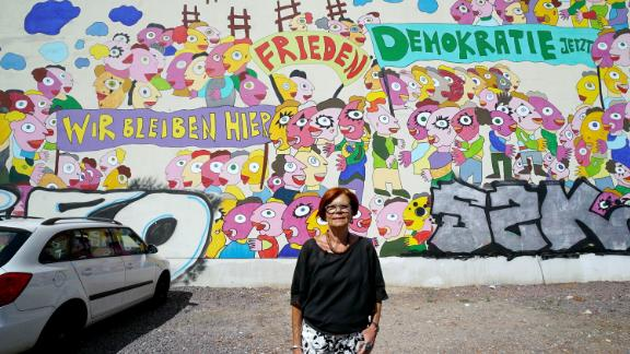 Retired Greens MEP, Gisela Kallenbach, poses in front of a mural depicting the 1989 protests.