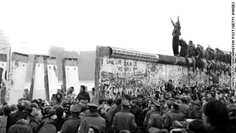 BERLIN - CIRCA NOVEMBER 1989:  People gather near a part of the Berlin Wall that has been broken down after the communist German Democratic Republic's (GDR) decision to open borders between East and West Berlin circa November 1989 in Berlin, West Germany. (Photo by Carol Guzy/The Washington Post/Getty Images)