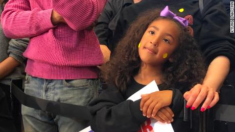 A young girl stands amid a diverse crowd at a Kamala Harris rally in Los Angeles.