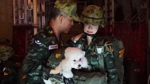 Thailand's King Maha Vajiralongkorn standing with Royal Noble Consort Sineenat Wongvajirapakdi and the royal dog.