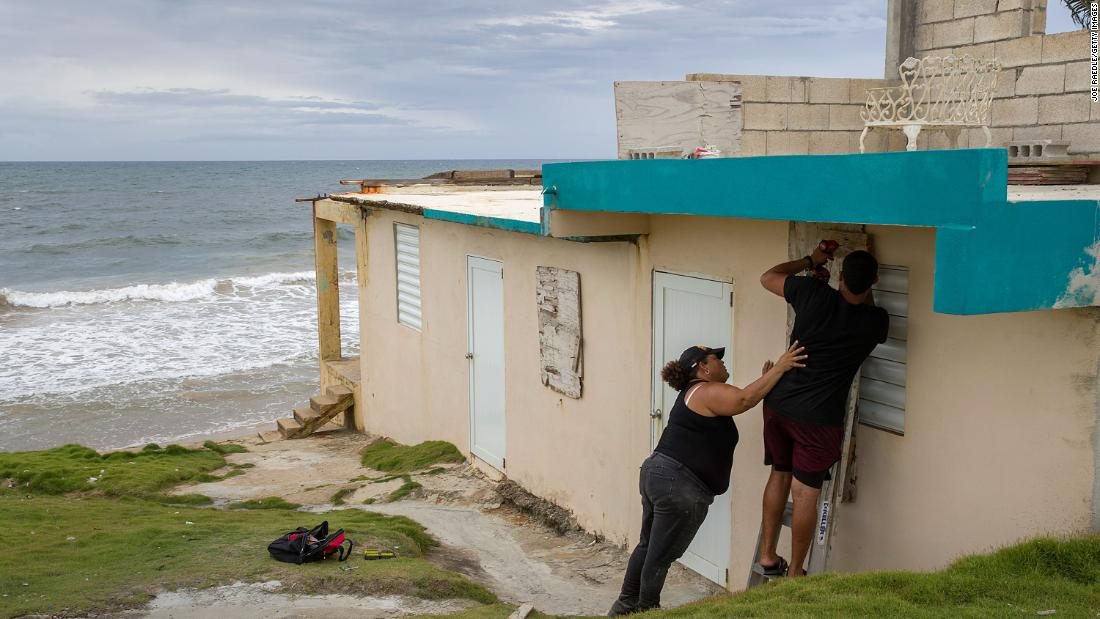 Ya Mary Morales and Henry Sustache put plywood over the windows of their home in Yabucoa, Puerto Rico, on August 28.