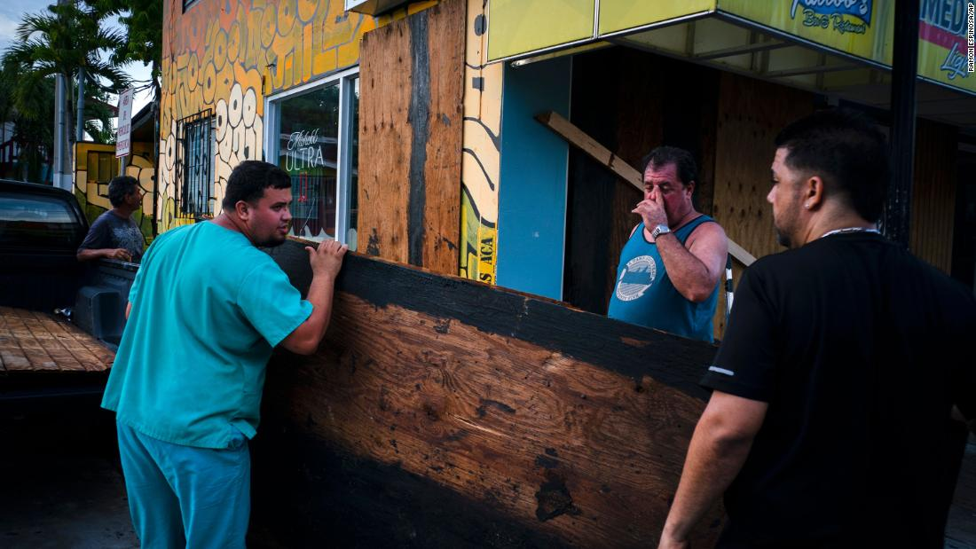 Men board up a shop's windows in Boqueron, Puerto Rico, on August 27.