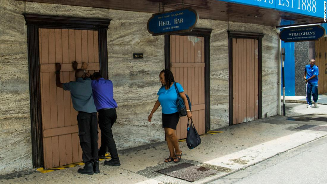 Residents board up a storefront pharmacy in Bridgetown, Barbados, on August 26.