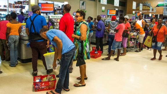 Residents stand in line at a grocery store in Bridgetown on August 26.