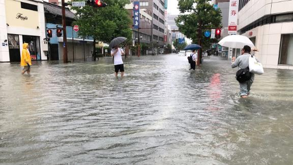 People walk in floodwaters after heavy rains in the southwestern city of Saga on August 28, 2019.