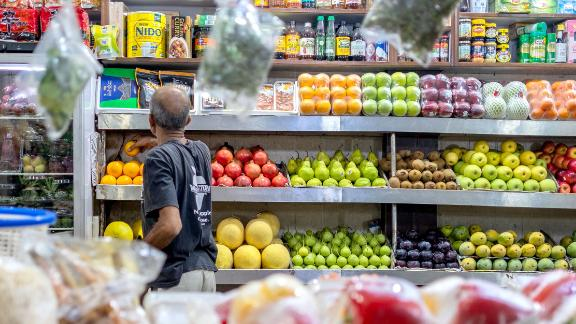A worker arranges fruits in his stall at the INA food market on August 25, 2019.