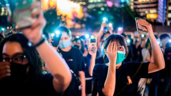 TOPSHOT - Secondary school students cover their right eye as they hold up their phone torches while attending a rally at Edinburgh Place in Hong Kong on August 22, 2019. - Hong Kong student leaders on Thursday announced a two-week boycott of lectures from the upcoming start of term, as they seek to keep protesters on the streets and pressure on the government. (Photo by Anthony WALLACE / AFP)        (Photo credit should read ANTHONY WALLACE/AFP/Getty Images)
