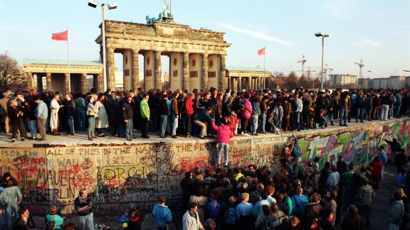 People climbing on the Berlin Wall at the Brandenburg Gate shortly after its opening