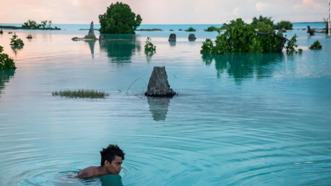 "Peia Kararaua, 16, swims in a flooded area of Kiribati's Aberao village. Kiribati is one of the countries most affected by sea-level rise, photographer <a href=""http://www.vladsokhin.com/"" target=""_blank"">Vlad Sokhin</a> said. During high tides many villages become inundated, making large parts of them uninhabitable. This photo was taken in an area that, when dry, is a soccer field. ""Prior to this, a man moved his vehicle from the lower part of the field to the higher point, and the vehicle ended up being parked on an 'island' when the water came,"" Sokhin said. ""Young people started swimming there and playing when I took this shot. It was strange to see such a scene: happy kids swimming along the remains of the dead palm trees."""