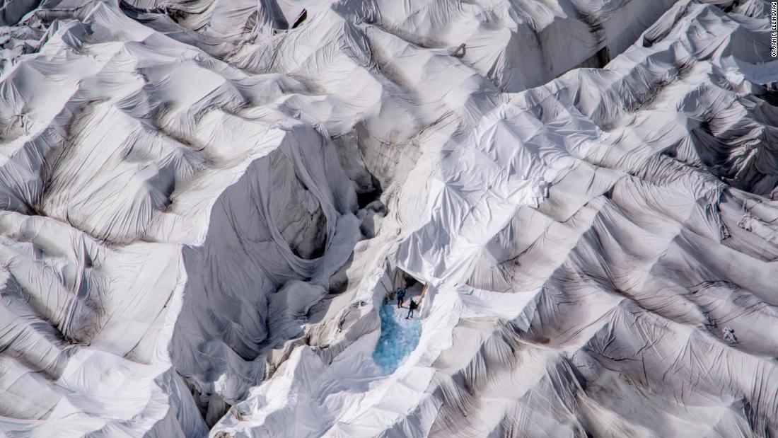 "Two people are seen at an ice cave entrance on the Rhone Glacier in the Swiss Alps. Every summer, the glacier is covered with huge sheets of white fleece blankets to slow down its melting, according to photographer <a href=""https://ellingvag.photoshelter.com/index"" target=""_blank"">Orjan F. Ellingvag.</a> ""The fleece-covered cave attracts more and more tourists worried about global warming and wanting to see the remnants of a dying glacier,"" Ellingvag said."