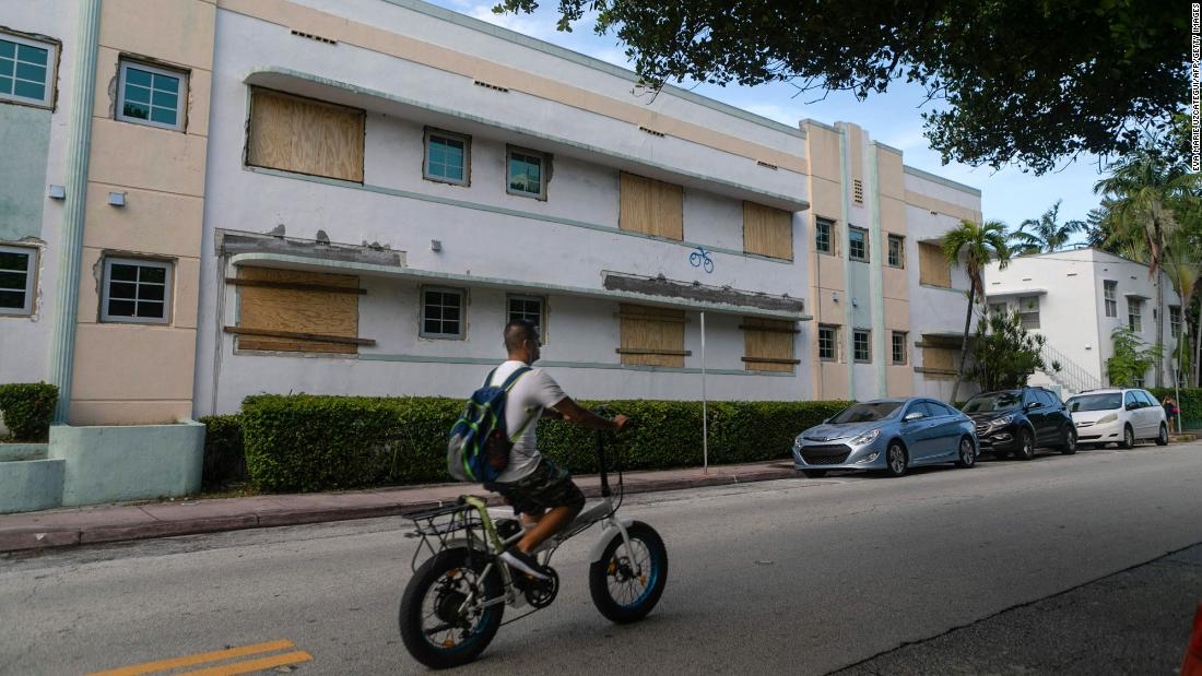 A man rides a bike by a Miami Beach building with boarded-up windows on August 29.