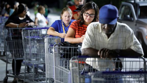 Shoppers wait in line before sunrise for a Sam