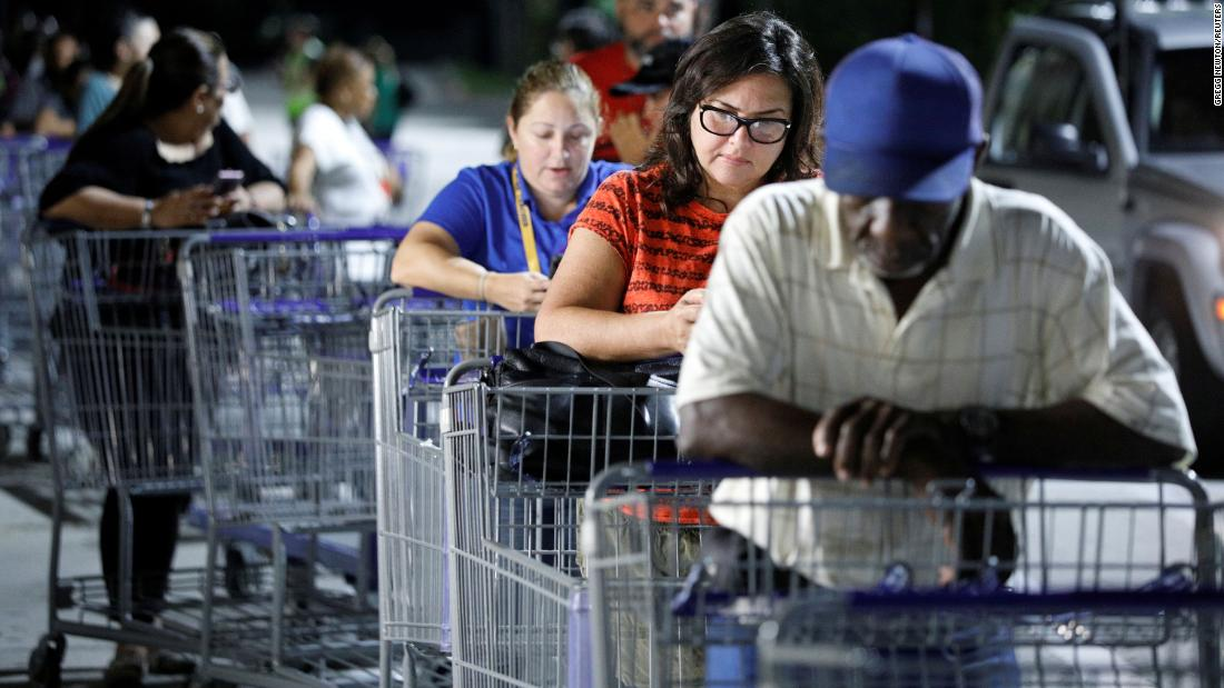 Shoppers wait in line before sunrise for a Sam's Club store to open in Kissimmee, Florida.