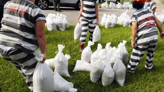 A supervised work crew of female jail prisoners fills sandbags in Titusville, Florida, on Thursday, August 29.