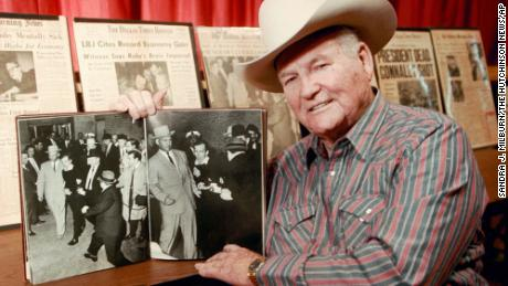 Jim Leavelle, seen here in 1998, holds the photograph showing him handcuffed to Lee Harvey Oswald when Oswald was shot by Jack Ruby.