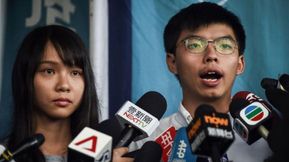 Pro-democracy activists Agnes Chow and Joshua Wong speak to the media after they were released on bail at the Eastern Magistrates Courts on Friday, August 30. They were arrested earlier the same day in a dragnet across Hong Kong.