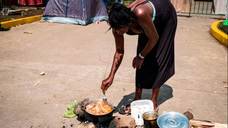 A migrant from Angola who is six months pregnant cooks in the street in front of Siglo XXI immigration facility.