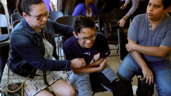 Gary Sanchez, of Honduras, right, watches as his wife, Mariela comforts their son, Jonathan, 16, during a news conference, Monday, Aug. 26, 2019, in Boston. The Sanchez family came to the United States seeking treatment for Jonathan