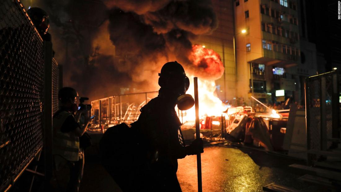Protesters stand in front of a burning barricade as clashes with the police intensified on August 31.