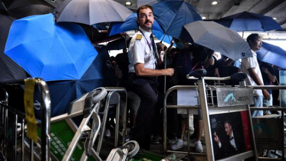 An airline crew member makes his way through a barrier set up by protesters at Hong Kong International Airport on September 1, 2019.