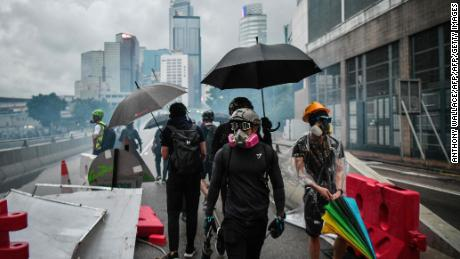Protesters gather in front of the Hong Kong government headquarters on August 31, 2019, as police tear gas on a street.