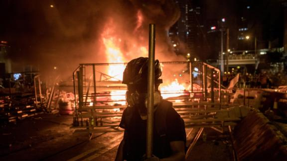 "HONG KONG, CHINA - AUGUST 31: A protesters walks in front of a burning barricade  after clashing with police at an anti-government rally on August 31, 2019 in Hong Kong, China. Pro-democracy protesters have continued rallies on the streets of Hong Kong against a controversial extradition bill since 9 June as the city plunged into crisis after waves of demonstrations and several violent clashes. Hong Kong's Chief Executive Carrie Lam apologized for introducing the bill and declared it ""dead"", however protesters have continued to draw large crowds with demands for Lam's resignation and completely withdraw the bill.  (Photo by Chris McGrath/Getty Images)"