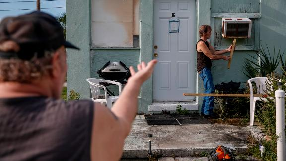 Riverside Mobile Home Park residents Joe Lewis, left, and Rob Chambers work to secure an air conditioner before evacuating the park in Jensen Beach, Florida.