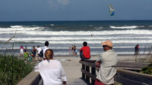 Beachgoers watch a man ride a kiteboard in Indialantic, Florida, on Sunday, September 1.