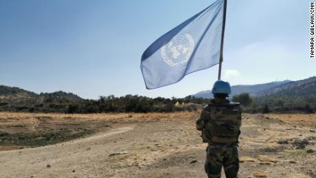 Outside the disputed Shebaa Farms, an Indian UN peacekeeper raises the UN flag to mark the demarcation line between Israel and Lebanon.