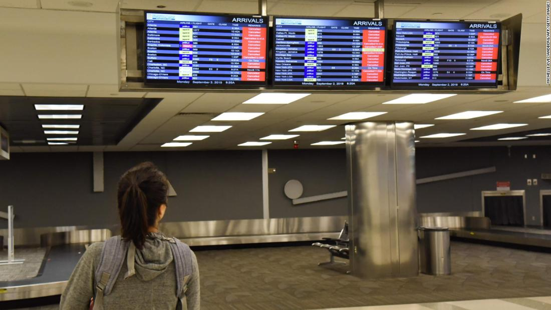 A passenger looks at the flight board at the Fort Lauderdale-Hollywood International Airport on September 2. The airport canceled flights and closed because of winds caused by Dorian.