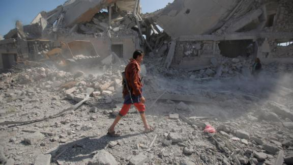 A Yemeni man walks amid the rubble of a Houthi detention center destroyed by Saudi-led airstrikes, that killed at least 60 people and wounding several dozen according to officials and the rebels