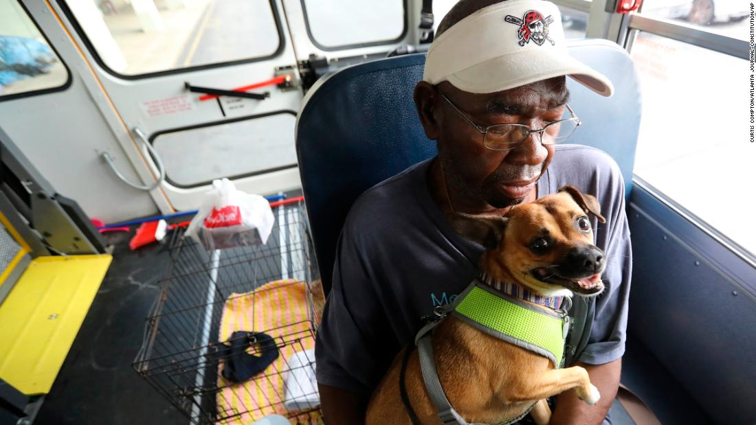Eddie Wright and his dog, Vino, wait on a bus to evacuate Brunswick, Georgia.