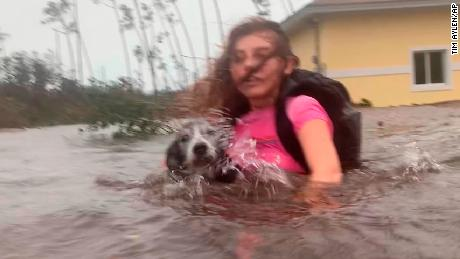Julia Aylen wades through waist deep water carrying her pet dog as she is rescued from her flooded home during Hurricane Dorian in Freeport, Bahamas, Tuesday, Sept. 3, 2019. Practically parking over the Bahamas for a day and a half, Dorian pounded away at the islands Tuesday in a watery onslaught that devastated thousands of homes, trapped people in attics and crippled hospitals. (AP Photo/Tim Aylen)
