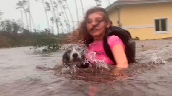 Julia Aylen carries her dog as she wades through waist-deep water near her home in Freeport on September 3.