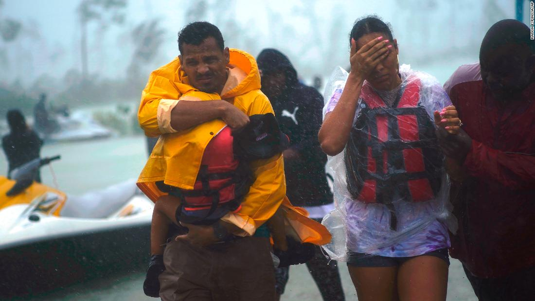 A family is escorted to a safe zone after being rescued, as Hurricane Dorian dumped rain in Freeport, Bahamas, on  September 3.
